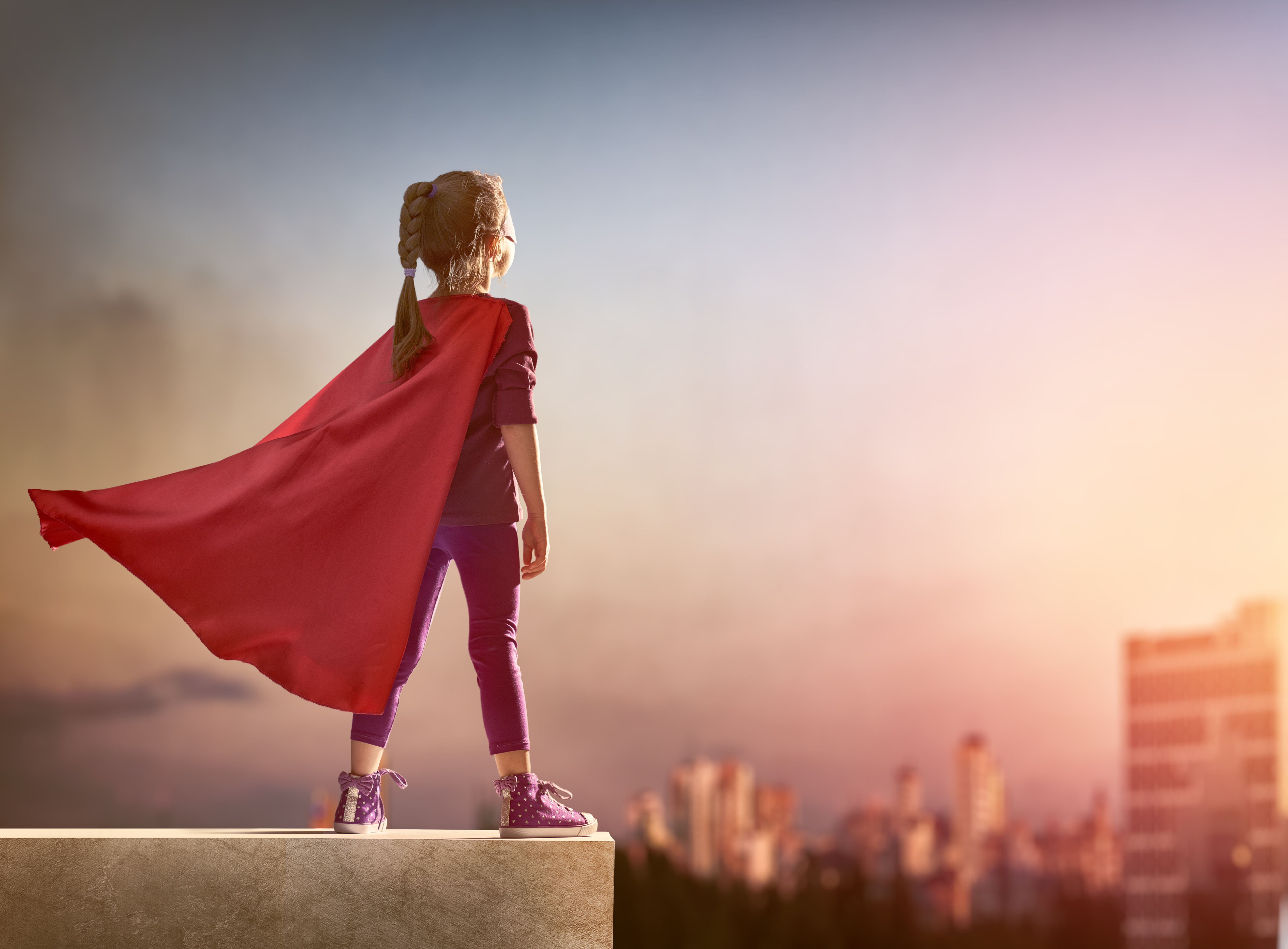female leadership - young girl in red cape looking out over the city